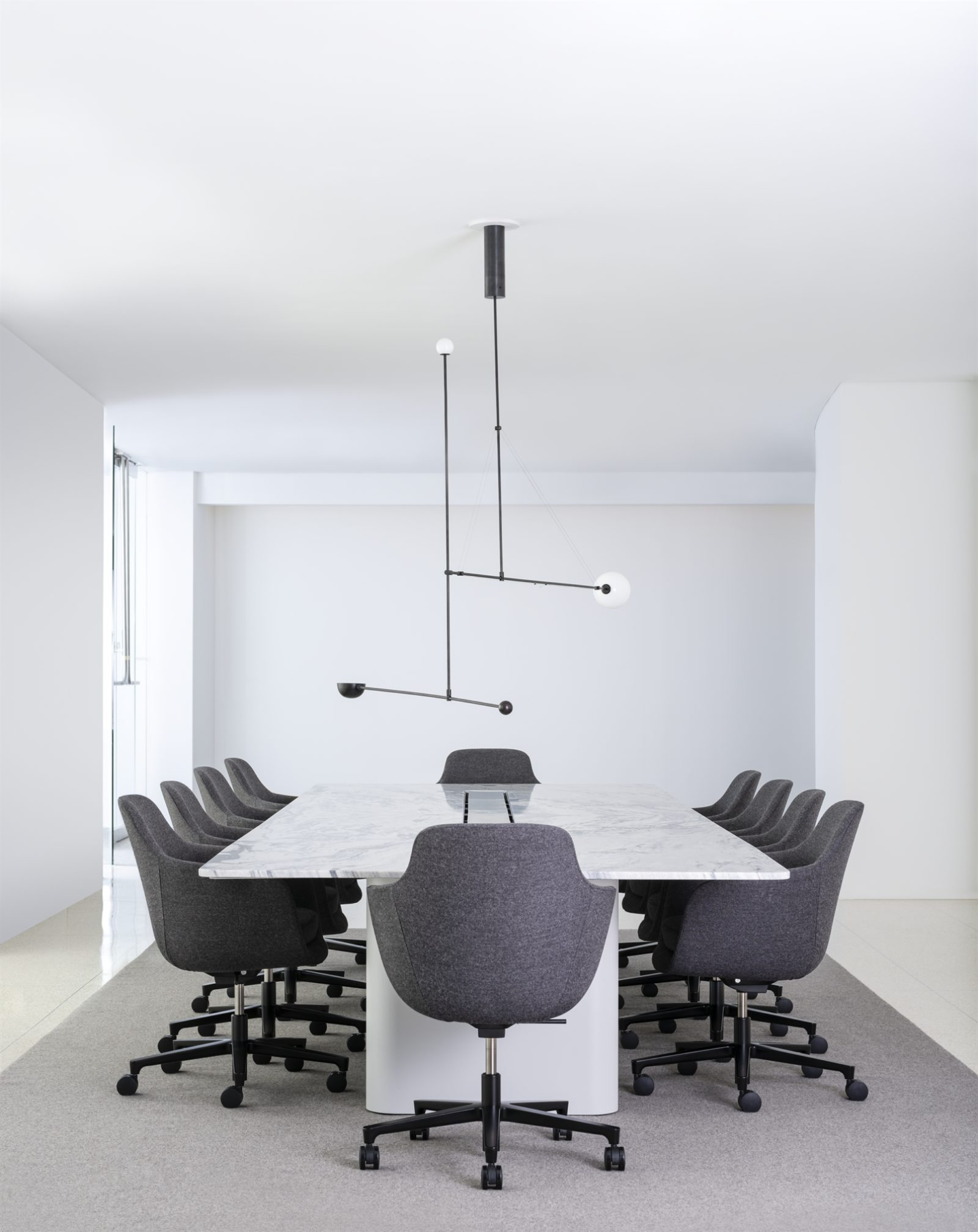 large white conference table with black chairs